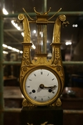 Empire Lyre style clock in gilded bronze, France 18th century